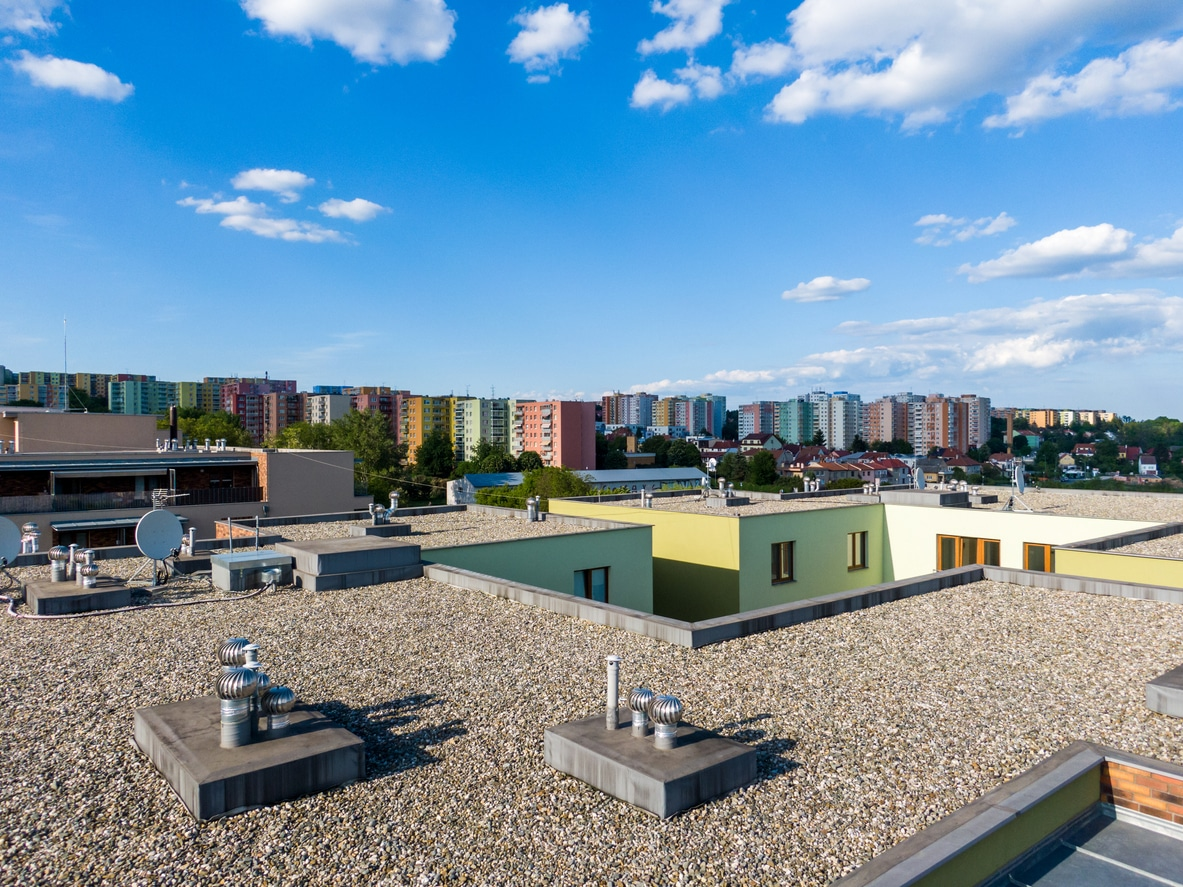 Aerial view of house flat roof on residental building. Modern architecture exterior. Air conditioning systems and ventilation structure. Residental building in background, sunny day.