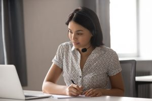 Asian businesswoman wear headset watching webinar make call write notes