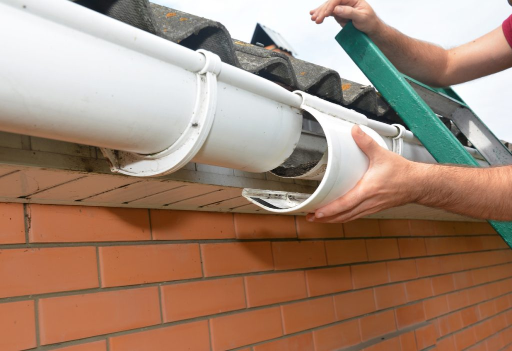 Roof gutter repair. Guttering repair. Roofer contractor repair house rain gutter pipeline.
