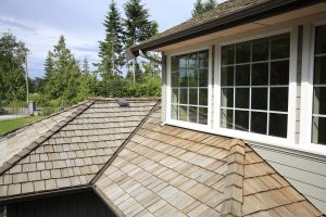 Close up looking down of New Cedar Shingle roof,gutters ,eaves and paned windows on a new home.