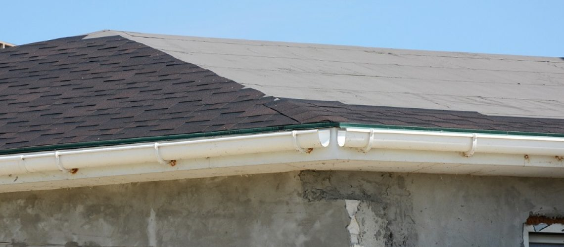 Roofing constraction. Install house roof gutter and laying asphalt shingles. Roof repair.